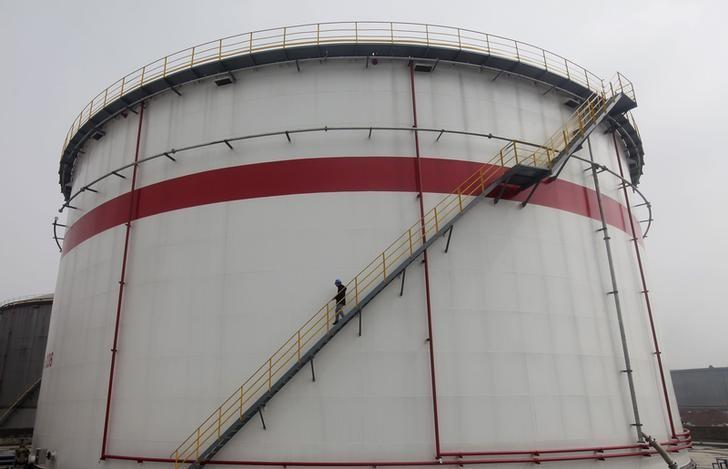A worker walks down stairs of an oil tank at a refinery in Wuhan, Hubei province March 23, 2012. REUTERS/Stringer