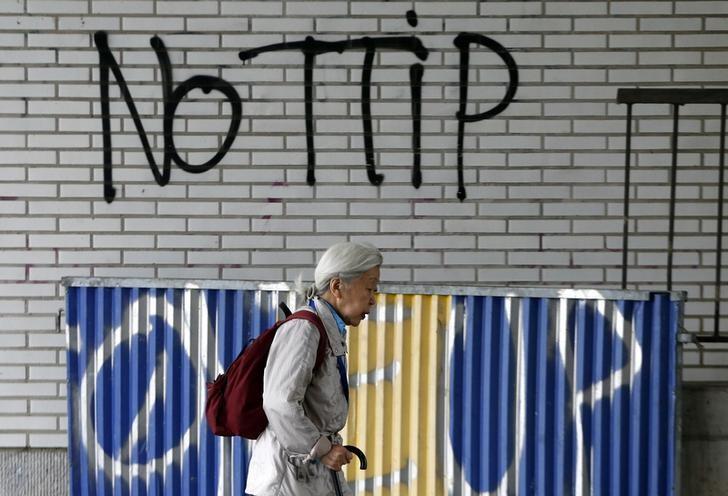 A pedestrian walks past graffiti that reads, ''No TTIP'', in Brussels, Belgium, July 27, 2015.       REUTERS/Francois Lenoir