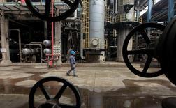 Un trabajador camina junto a los oleoductos en una refinería en Wuhan, provincia de Hubei, China. 23 de marzo de 2012. La producción de petróleo de China cayó un 9,8 por ciento en septiembre respecto al mismo mes del año anterior, lo que representa su segunda mayor caída interanual desde que hay registros, mostraron datos del Gobierno.  REUTERS/Stringer/File Photo