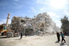 """Люди рассматривают место авиаудара в удерживаемом повстанцами пригороде сирийского Алеппо 17 октября 2016 года. Высокопоставленные американские и российские чиновники в среду провели переговоры, направленные на согласование того, как отделить связанных с """"Аль-Каидой"""" боевиков от повстанцев в осажденном сирийском Алеппо, создав почву для перемирия. REUTERS/Abdalrhman Ismail"""