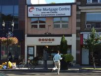 A man crosses the street in front of a mortgage brokerage office above a bakery, on Danforth Avenue in Toronto, Ontario, Canada on September 17, 2013.   REUTERS/Chris Helgren/File Photo