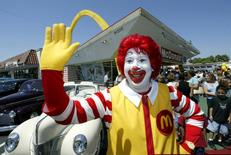 A Ronald McDonald character poses at the world's oldest operating McDonald's restaurant, with the original golden arch architecture, as it draws a crowd on its 50th anniversary in Downey, California, August 18, 2003.   REUTERS/Fred Prouser/File Photo