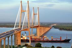 Un barco carguero atravesando el Puente Rosario-Victoria en el río Paraná, Argentina, feb 1, 2006. Un grupo de firmas agroexportadoras invertirá 1.210 millones de dólares en los próximos tres años en la mayor central de puertos agrícolas y plantas procesadoras de granos de Argentina, uno de los principales proveedores globales de alimentos, anunció el viernes el Gobierno.  REUTERS/Alfredo Celoria - RTR1ACI0
