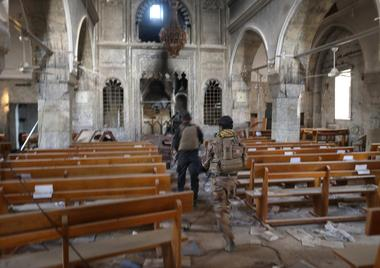 Iraqi special forces soldiers walk inside a church damaged by Islamic...