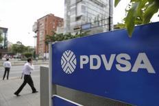 Una persona camina cerca del logo de PDVSA en una gasolinera en Caracas. La estatal Petróleos de Venezuela (PDVSA) informó el lunes que logró postergar hasta el 2020 el pago de unos 2.798 millones de dólares en bonos que vencían en 2017, al canjear el equivalente a un 39,4 de sus notas en manos de inversores. REUTERS/Marco Bello