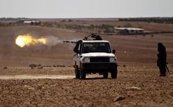 Combatantes rebeldes atirando contra a cidade de Dabiq .   16/10/2016       REUTERS/Khalil Ashawi