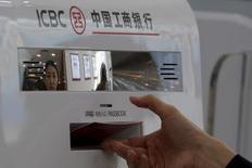 Банкомат  ICBC в отделении банка в Пекине. Industrial and Commercial Bank of China (ICBC), крупнейший по объёму активов банк, акции которого котируются на бирже, отчитался в пятницу о небольшом снижении квартальной прибыли в связи с проблемными кредитами и низкой ссудной маржой.  REUTERS/Kim Kyung-Hoon