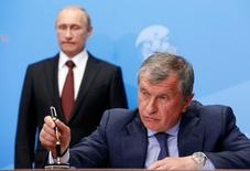 Russia's President Vladimir Putin (back) and Rosneft CEO Igor Sechin attend a signing ceremony at the St. Petersburg International Economic Forum 2014 (SPIEF 2014) in St. Petersburg, Russia, May 24, 2014.     REUTERS/Sergei Karpukhin/File Photo - RTX2DM2Z