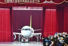 People take pictures and videos as the first C919 passenger jet made by the Commercial Aircraft Corp of China (Comac) is pulled out during a news conference at the company's factory in Shanghai, November 2, 2015. REUTERS/Stringer