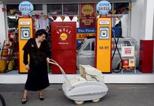 A woman holds the handle of an old pram in front of vintage Shell petrol pumps at the annual Goodwood Revival historic motor racing festival, near Chichester, Britain September 9, 2016. REUTERS/Toby Melville/File Photo