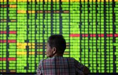 Китайский инвестор сидит перед табло с данными об акциях. Китайский рынок вырос после того как частное исследование обнаружило признаки экономической стабильности в стране; кроме того, настроения рынка поддержало и предстоящее внедрение механизма перекрёстных торгов между биржами Шэньчжэня и Гонконга.  China Daily/via REUTERS