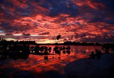 Las principales compañías petroleras como Aramco de Arabia Saudi, Royal Dutch Shell y Total se comprometieron el viernes a invertir 1.000 millones de dólares en tecnologías de reducción de emisiones de dióxido de carbono para ayudar a combatir el calentamiento global. En la imagen de archivo, habitantes del pueblo de Tangintebu en la isla de Kiribati en el Pacífico central, el 25 de mayo de 2013. REUTERS/David Gray