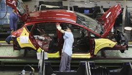 Un trabajador brasileño ensambla un auto Ford en San Bernardo, cerca de San Pablo, Brasil. 13 de Agosto, 2013. La producción de automóviles en Brasil subió un 2,3 por ciento y las ventas cayeron un 0,6 por ciento en octubre frente a septiembre, dijo el lunes la asociación nacional de fabricantes, Anfavea. REUTERS/Nacho Doce