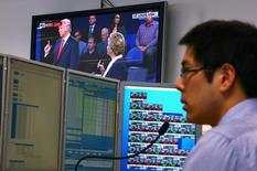 A trader works at his desk as the U.S. presidential town hall debate between Republican U.S. presidential nominee Donald Trump and Democratic nominee Hillary Clinton is shown on television at Citibank's trading floor located in central Sydney, Australia, October 10, 2016. REUTERS/David Gray