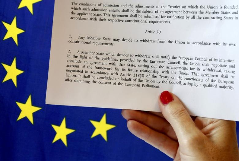 Article 50 of the EU's Lisbon Treaty that deals with the mechanism for departure is pictured near an EU flag following Britain's referendum results to leave the European Union, in this photo illustration taken in Brussels, Belgium, June 24, 2016. REUTERS/Francois Lenoir/Illustration/Files