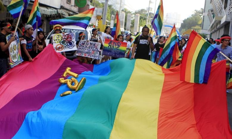 Members of the Lesbians, Gays, Bisexuals and Transgenders (LGBT) community hold rainbow flags and placards during a march in Makati City, Metro Manila October 11, 2015. REUTERS/Janis C. Alano