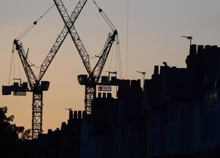 Construction cranes are seen on a residential building project behind homes in west London in Britain, October 26, 2016. REUTERS/Toby Melville/Files