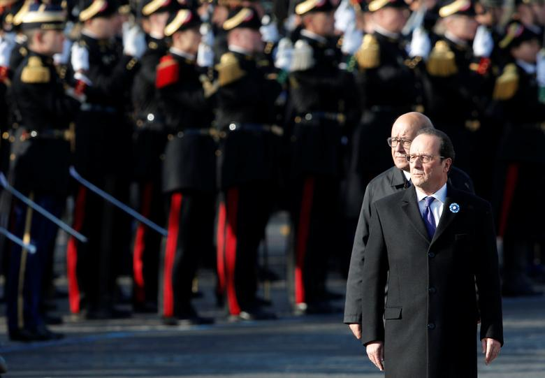 France's President Francois Hollande (R) and Defence Minister Jean-Yves Le Drian review troops as they attend a commemoration ceremony for Armistice day, 98 years after the end of the First World War at the Arc de Triomphe in Paris, France, November 11, 2016. REUTERS/Christian Hartmann