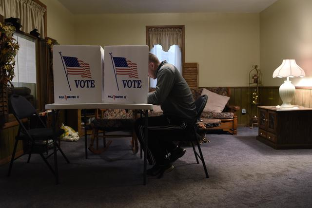 A voter fills out his ballot in a living room polling place in Dover, Oklahoma. REUTERS/Nick Oxford