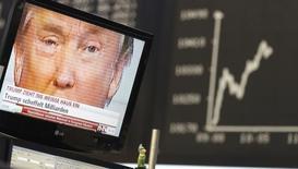 Избранный президентом США Дональд Трамп на телеэкране рядом с табло, отражающим динамику курсов акций на фондовой бирже Франкфурта 9 ноября 2016 года. Трамп лишь отчасти исполнит предвыборное обещание ослабить регулирование финансового сектора, введенное шесть лет назад, написала газета Wall Street Journal со ссылкой на неназванные источники. REUTERS/Kai Pfaffenbach