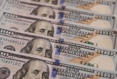 Банкноты в 100 долларов. Доллар достиг пика девяти месяцев к корзине шести основных валют в понедельник на фоне роста доходности госбондов США и, вероятно, готовится к возобновлению бычьих настроений на рынке после победы Дональда Трампа на президентских выборах в США.  REUTERS/Valentyn Ogirenko/Illustration