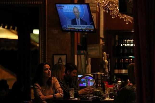 11月14日、オバマ米大統領は記者会見で、トランプ氏について、来年の大統領就任後直ちに重大な職責と現実に直面することになるだろうと述べた。ニューヨークのトランプ・タワー内のバーでテレビ放映を見る女性(2016年 ロイター/Carlo Allegri)