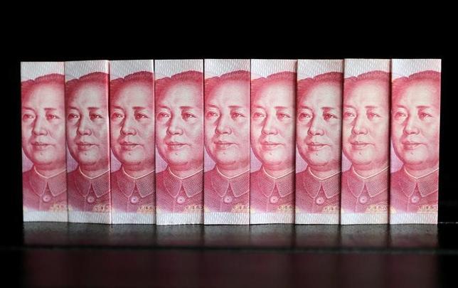 11月13日、中国政府が資金の国外流出防止に躍起となる中、国内の景気減速や人民元安を嫌い、規制をすり抜けて出ていく資金の規模は拡大の一途をたどっている。写真は人民元紙幣。北京で2013年7月撮影(2016年 ロイター/Jason Lee)