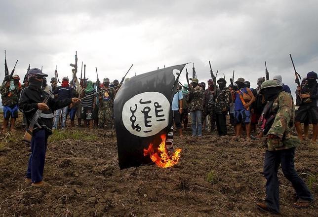 11月14日、フィリピンのドゥテルテ大統領は、シリアやイラクを追われた過激派組織「イスラム国」(IS)の戦闘員らがフィリピンに入国し活動拠点を築くこともあり得るとした上で、そうなった場合、人権に関する義務を放棄して国民の安全を守ると述べた。写真は、キリスト教徒の自警団「レッド・ゴッド・ディフェンダー」がイスラム国の旗を燃やしている模様。ミンダナオ島中部の潜伏拠点で1月撮影(2016年 ロイター)
