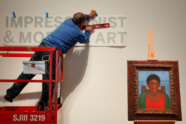 11月14日、これまで一度も公開されたことがなく、所在が謎に包まれていたフリダ・カーロの絵画「首飾りを付けた少女」が、来週ニューヨークでサザビーズのオークションにかけられることが分かった。写真は絵の横でオークションの準備をする男性(2016年 ロイター/Shannon Stapleton)