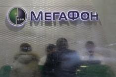 Клиенты в магазине Мегафона в Москве. Второй по доле рынка телекоммуникационный оператор Мегафон сообщил в среду, что ведет переговоры с некоторыми акционерами Mail.ru о вхождении в капитал интернет-компании.    REUTERS/Sergei Karpukhin (RUSSIA - Tags: BUSINESS TELECOMS)