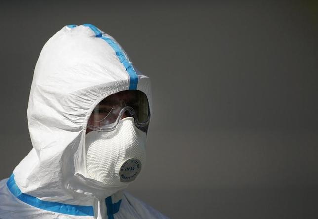 11月16日、ドイツ当局は、国内で病原性の高いH5N8型鳥インフルエンザが発生し、日本など数カ国がドイツの家禽輸入を規制していると明らかにした。写真は家禽農場のバイオハザードスーツを着た労働者。ドイツのヴァッヒェンロートで2007年8月撮影(2016年 ロイター/Hannibal Hanschke)