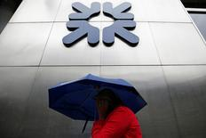 A woman shelters under an umbrella as she walks past a branch of the Royal Bank of Scotland in the City of London, Britain, September 17, 2013.  REUTERS/Stefan Wermuth/File Photo
