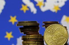 Monedas de euro frente a una bandera de la Unión Europea, 28 de mayo, 2015. La Unión Europea llegó a un acuerdo en las primeras horas del jueves sobre el presupuesto del próximo año, que aumentará el gasto gubernamental para crear más empleos y abordar la crisis de inmigración, pero Italia se abstuvo, en una nueva señal de la tensa relación de Roma con Bruselas. REUTERS/Dado Ruvic