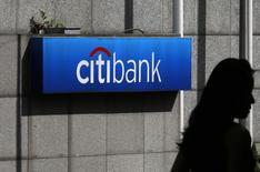 A woman walks past a Citibank logo displayed outside the Citibank Plaza in Hong Kong July 28, 2014.  REUTERS/Bobby Yip
