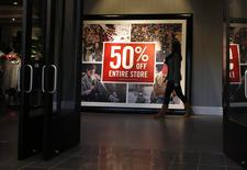 A woman walks by a discount sign at an Abercrombie & Fitch store at a shopping mall in Garden City, New York, U.S. on November 28, 2014. REUTERS/Shannon Stapleton/File Photo