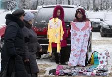 Женщины торгуют одеждой в Минске. 15 января 2013 года. Белоруссия рассчитывает, что Евросоюз снимет ограничения для белорусских товаров вслед за отменой политических санкций в феврале этого года, сказал белорусский президент Александр Лукашенко на встрече с европейской делегацией. REUTERS/Vasily Fedosenko