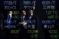 En la imagen, personas se reflejan en una pantalla electrónica que muestra información bursátil, afuera de una correduría en Tokio, Japón. 10 de febrero de 2016.El índice Nikkei de la bolsa de Tokio subió el lunes, en su cuarto sesión consecutiva de ganancias, luego de que un debilitamiento del yen aumentó la confianza de los inversores.  REUTERS/Thomas Peter/File Photo
