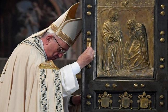 11月21日、ローマ法王フランシスコは21日、「いつくしみの特別聖年」終了に当たって公文書を発表し、妊娠中絶に対して「赦しの秘跡」を与える権限をカトリック司祭に無期限で拡大した。写真は20日代表撮影。法王が聖年終了にあたり聖なる扉を閉めるようす(2016年 ロイター/Tiziana Fabi)