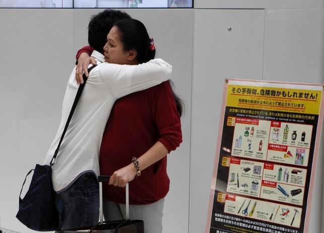 11月22日──9月半ば、朝の成田国際空港。16歳の少年ウティナン・ウォン(左)はタイに帰国する母を固く抱き締めた後、出発ゲートに消えていく後姿をじっと見送った。9月撮影(2016年 ロイター/Thomas Wilson)