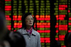 Una inversionista delante de un panel con información bursátil en una correduría en Shanghái, China, nov 9, 2016. Las acciones chinas avanzaron el martes a un nuevo máximo en 10 meses y medio, impulsadas por un fuerte repunte de los principales valores, en particular del sector financiero y de energía.   REUTERS/Aly Song