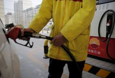 A gas station attendant puts fuel into a customer's car at PetroChina's filling station in Beijing, China, March 21, 2016.   REUTERS/Kim Kyung-Hoon
