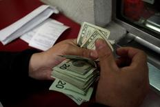 Сотрудник обменного пункта в Монтеррее пересчитывает доллары США. Доллар укрепился на торгах в Азии в четверг после того, как данные, указывающие на ускорение роста экономики США в начале четвёртого квартала, увеличили шансы на повышение ставки ФРС.  November 9, 2016. REUTERS/Daniel Becerril