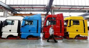 La tasa de crecimiento de la economía alemana se redujo a la mitad en el tercer trimestre a un 0,2 por ciento, pese a un aumento del consumo privado y un mayor gasto estatal, después de que de que un débil comercio exterior ralentizase la actividad general en la mayor economía de Europa. En la imagen de archivo, un hombre cruza una planta de producción de camiones y autobuses de MAN AG en Múnich, Alemania. 30 de julio de 2015. REUTERS/Michaela Rehle