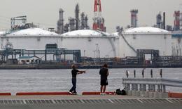 Люди рыбачат у НПЗ в Кавасаки. 5 июля 2012 года. Цены на нефть стабилизировались в преддверии саммита ОПЕК, на котором членам картеля предстоит обсудить реализацию соглашения о сокращении объёмов добычи. REUTERS/Toru Hanai/File Photo