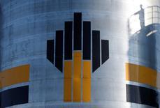 Foto de archivo de la sombra de un trabajador petrolero cerca del logo de Rosneft en un campo en las afueras de Nefteyugansk, en Siberia. Ago 4, 2016. Rosneft, la mayor productora de petróleo de Rusia, dijo el jueves que retornará al mercado doméstico de deuda tras una ausencia de dos años con un programa por 1,071 billones de rublos (16.600 millones de dólares). REUTERS/Sergei Karpukhin