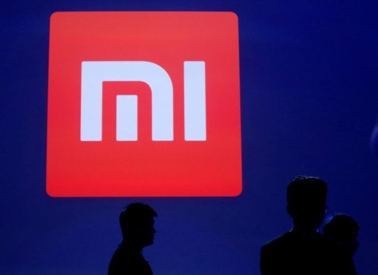 Attendants are silhouetted in front of Xiaomi's logo at a venue for the launch ceremony of Xiaomi's new smart phone Mi Max in Beijing, May 10, 2016. REUTERS/Kim Kyung-Hoon/File Photo