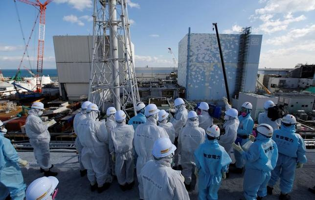 Members of the media, wearing protective suits and masks, receive briefing from Tokyo Electric Power Co. (TEPCO) employees (in blue) in front of the No. 1 (L) and No.2 reactor buildings at TEPCO's tsunami-crippled Fukushima Daiichi nuclear power plant in Okuma town, Fukushima prefecture, Japan February 10, 2016. REUTERS/Toru Hanai/File Photo