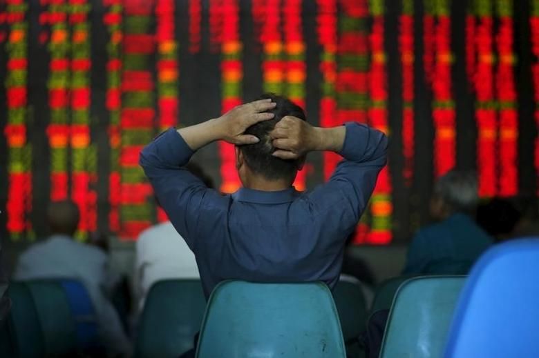 2015年5月12日,上海一家券商营业部,股民们在看大屏幕上的股票信息。REUTERS/Aly Song