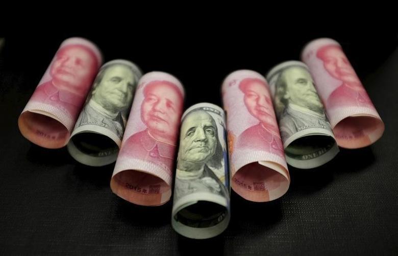 2016年1月21日,百元面值的人民币纸币和美元纸币。REUTERS/Jason Lee