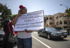Uber driver Sam Salem, 29, protests with other commercial drivers with the app-based, ride-sharing company Uber against working conditions outside the company's office in Santa Monica, California June 24, 2014. REUTERS/Lucy Nicholson/File Photo